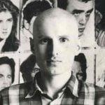 Marek Bajun na tle narysowanych ołówkiem portretów